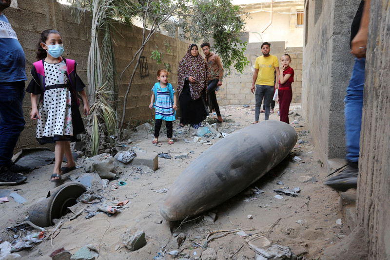 Men, women and children stand near large missile in narrow alley