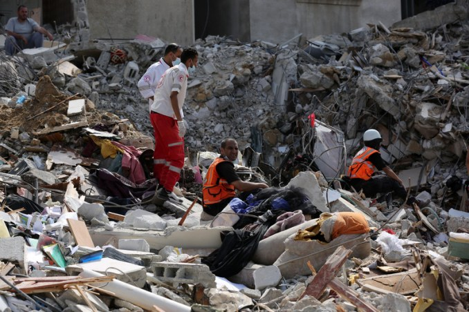 Rescue workers search in rubble from destroyed building