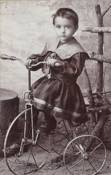 ребенок на старинном трехколесном велосипеде