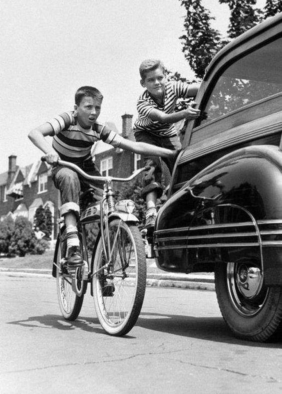 пацан на старинном велосипеде цепляется к машине