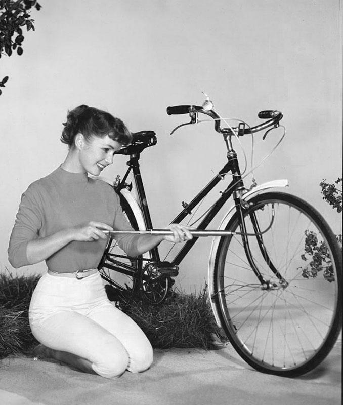 Актриса Дебби Рейнольдс накачивает шину велосипеда.