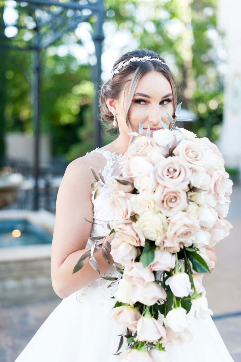 Bride holding flowers in front of Grand Island Mansion