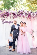 Family standing in front of beautiful pink photo backdrop