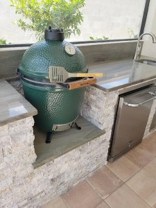 Close-up Of Big Green Egg and Silver Travertine Stacked Stone Facade & Upgraded Wild Sea Green Granite