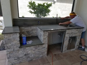 Elegant Outdoor Kitchens doing Some Countertop Finishing Work