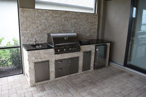 Light Travertine Stacked Stone Facade and Backsplash with Peacock Green Granite