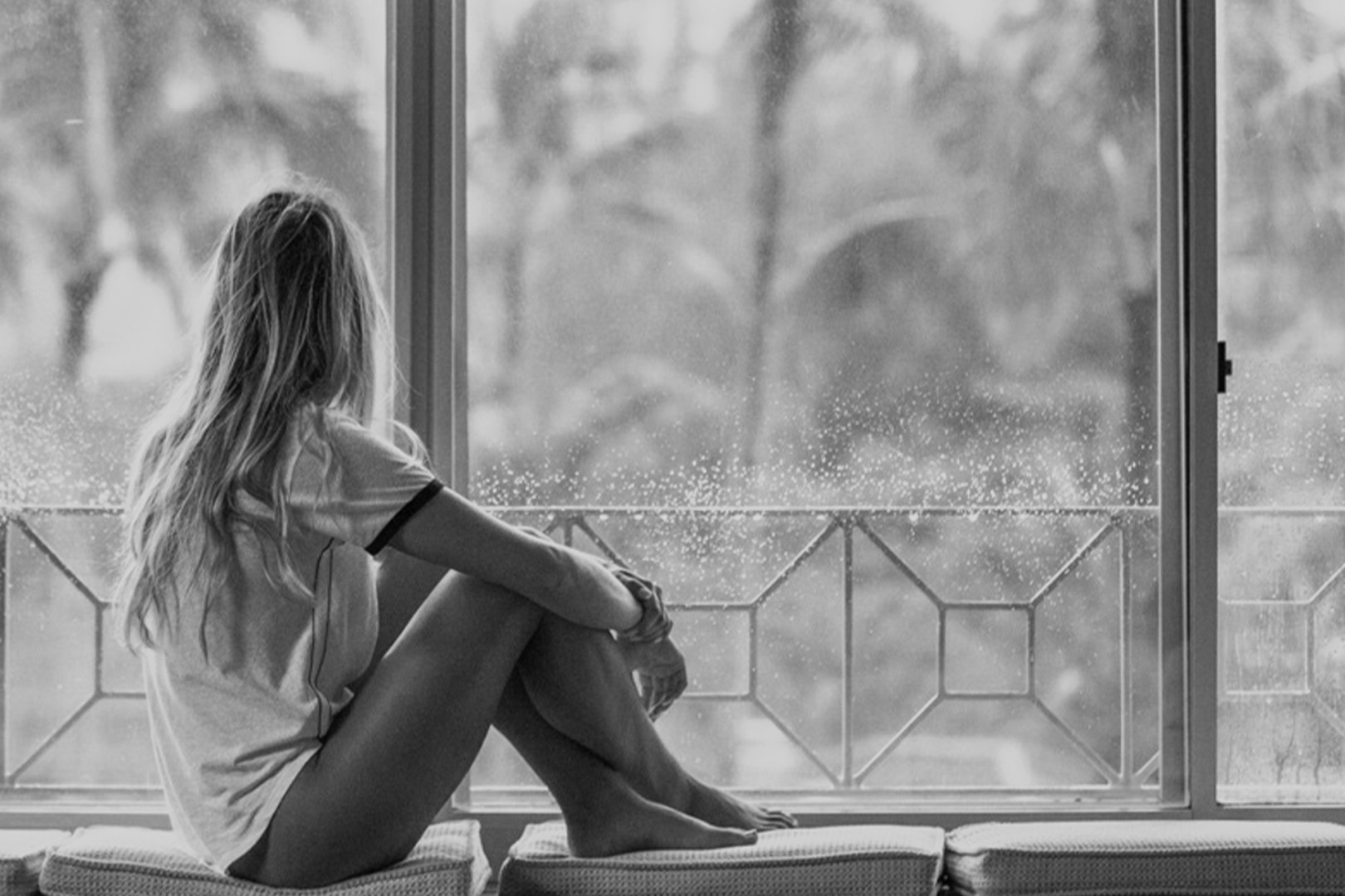 A black and white picture of a young woman looking out the window on a rainy day.