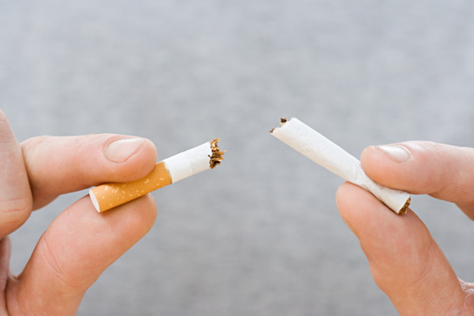 A closeup of two hands breaking a cigarette in two.