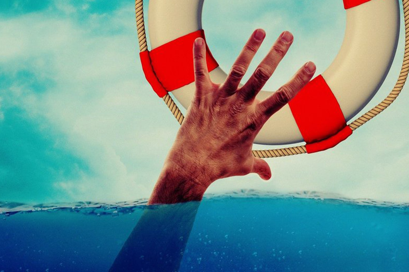 A man's hand reaching out of water for a lifebuoy.