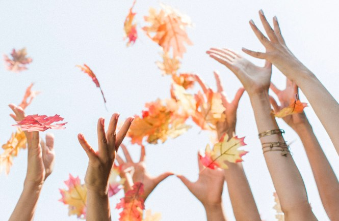 People throwing fall leaves into the air