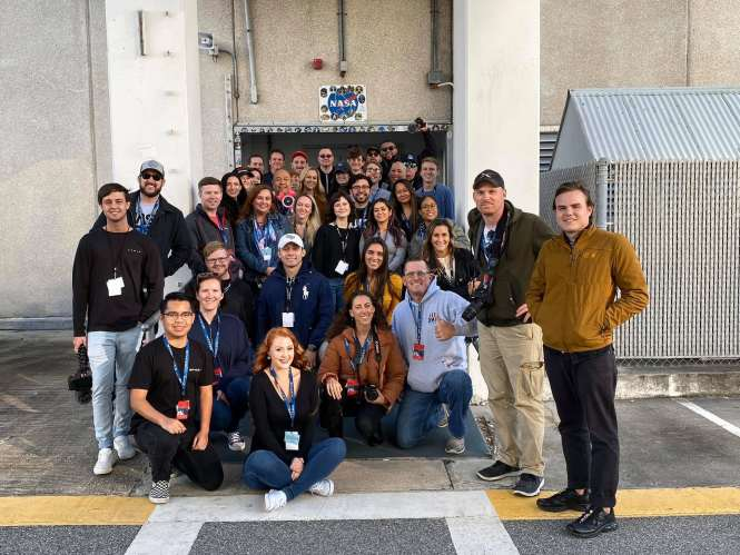 NASA Social participants posing outside the astronaut walkout ramp outside the crew quarters at Kennedy Space Center.