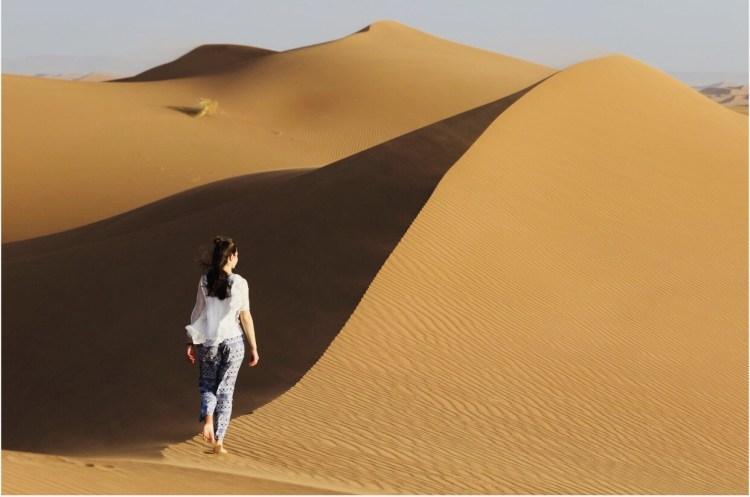 Ragazza che cammina sulle dune di sabbia del deserto del Sahara in Marocco
