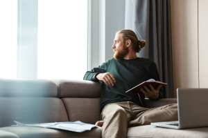 Man looking out a window from his sofa