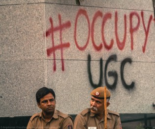 """Why 'occupy'? Some of the participants told me that the demonstrations drew inspiration from the Western protest culture of 'occupation', made virulently famous by the momentous """"#OccupyWallStreet"""" movement that held to moral hostage America's corporate power corridors for a long time (still does). Highly potent in its design and character, occupation is a relatively newer idea in India. The disruptive and continuous intrusion into the physical space of a building effortlessly translates into massive symbolic meaning. It is a form of protest that is explicit and powerful - precisely why the State invests considerably in keeping the agitators at bay. While the protestors aim towards creating physical conditions for limiting the free movement space for administrative officials, the State persistently tries to visibly overawe and subdue the spirits of the agitators by maintaing a tight cop cover. An occupation, moreover, provides a constant view of the power corridors that demonstrators are fighting against."""