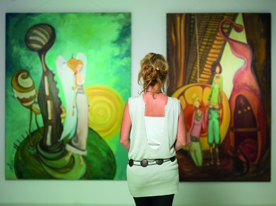 woman contemplating colorful paintings