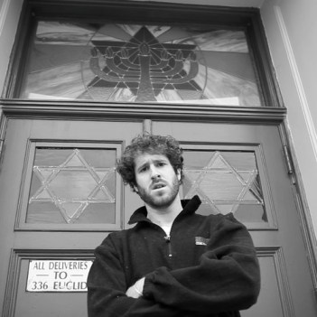 "Burd standing in front of a synagogue as part of his ""All K"" video"