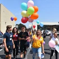 Freshmen and their Link Crew leader tour around the Small Gym holding balloons