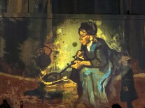 Flames glow a brilliant yellow behind Van Gogh's Peasant Woman Cooking by a Fireplace.