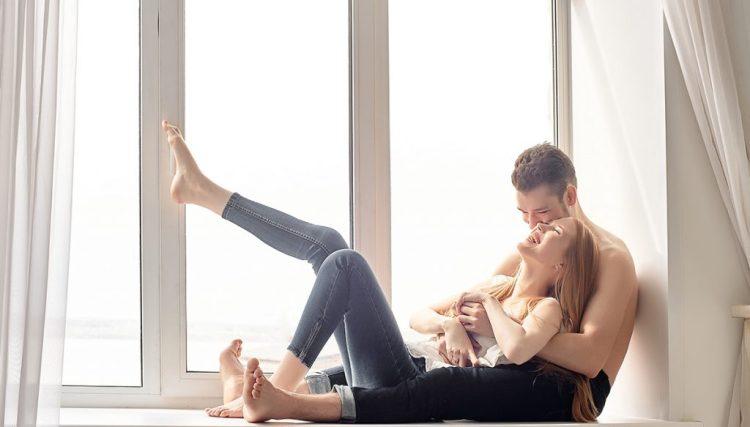 una pareja disfruta un momento tierno frente a la ventana