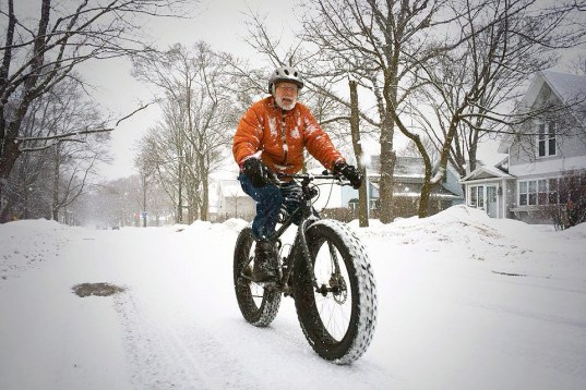 Older man winter biking in the snow.