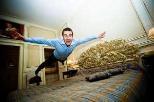 Homem voando sobre a cama