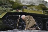 Russian war veteran kneels beside the tank he spent the war in, now a monument