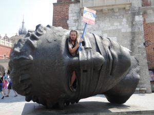 """Cadeau : notre guide touristique dans la sculpture """"grosse tête"""" sur la place du marché de Cracovie en Pologne"""