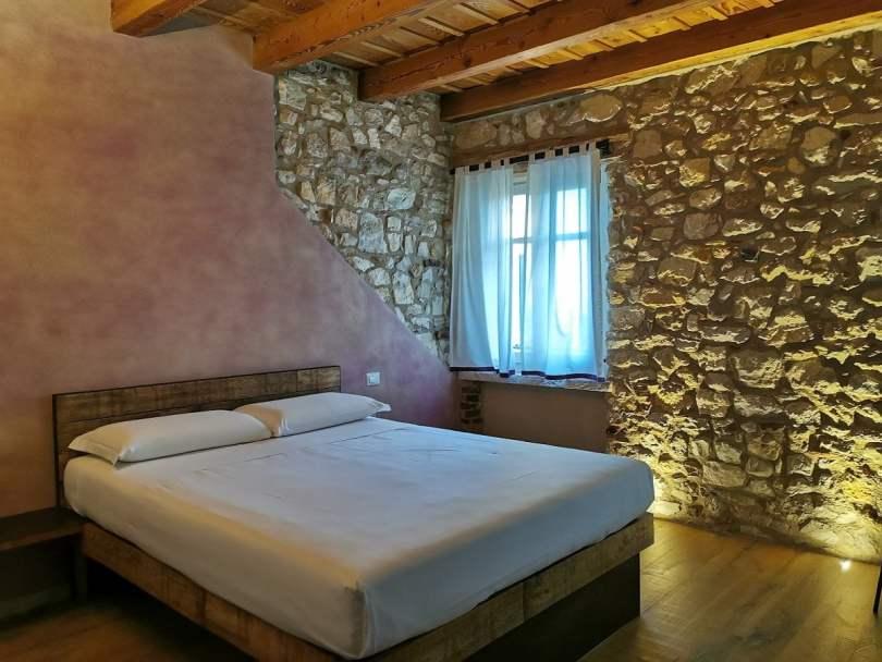 Stanza La Vigna a Corte Formigar_stanza da letto con mattoni a vista e travi