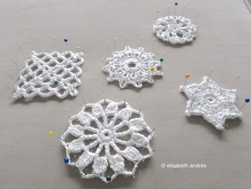 white crochet motifs with glittter pinned and drying