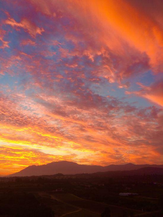 Den nedåtgående solen över Andaluciens berg bildar eldsflammor på  himlen.