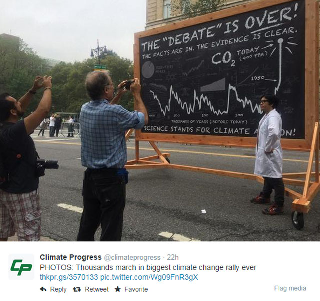 People's Climate March NYC -- photo with sign on chalkboard and graph: The (climate change) debate is over!