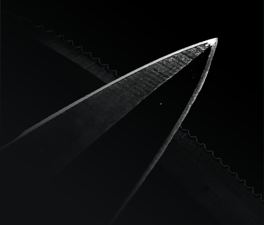 a dark knife on a black background with a serrated blade visible behind