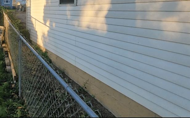 Fence close to vinyl siding on a house