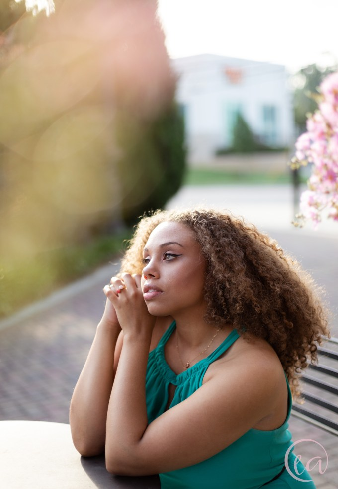 Kaela clasps her hands and gazes out of frame as she sits beneath a blossoming tree. Elizabeth A. Images