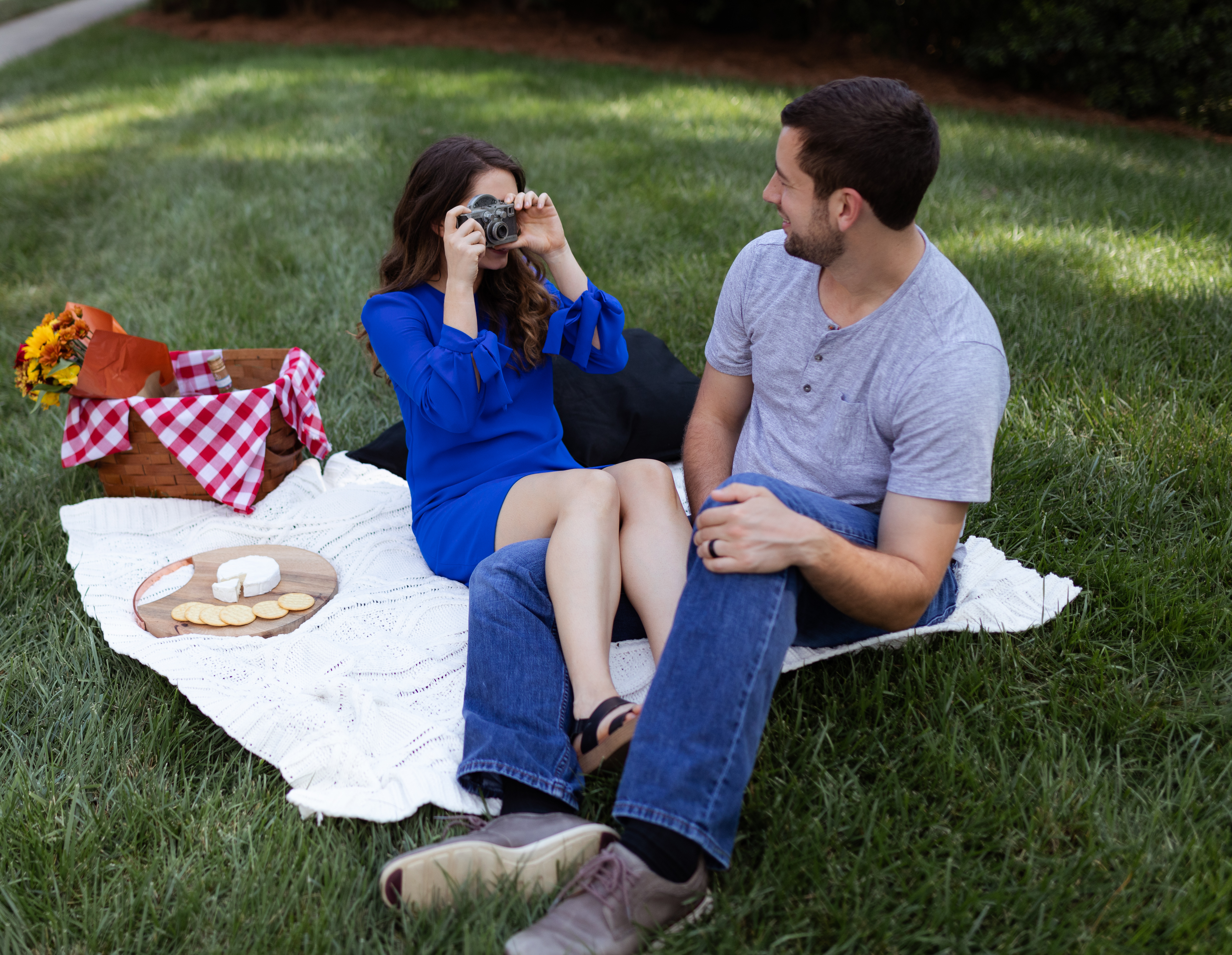 Kelly snaps a photo of her husband on a vintage camera during their picnic. couple portrait by Elizabeth A. Images