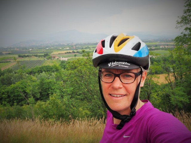 Selfie of a woman in bicycling helmet with Italian valley landscape behind her.