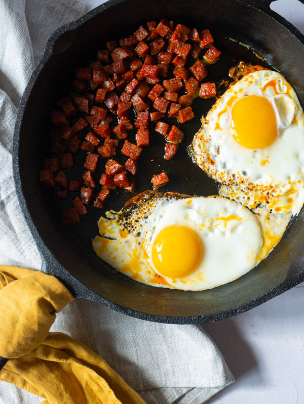 cooked eggs and chorizo in a cast iron frying pan