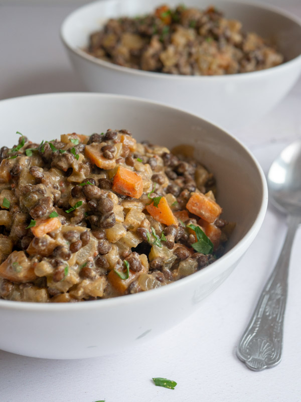 two bowls of mustard lentil stew and a silver spoon