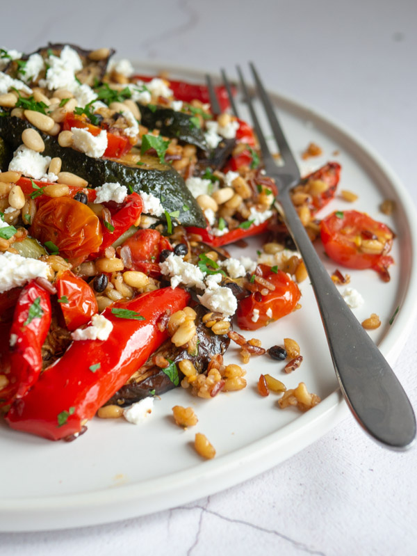 roasted vegetables feta and grains on a white plate