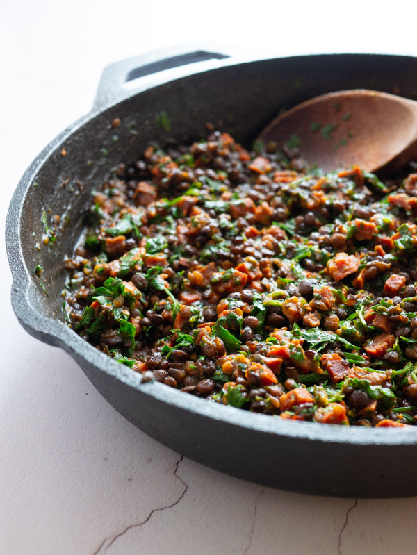 chorizo, lentils, spinach and parsley cooking in a cast iron skillet