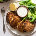Pea and salmon fishcakes on a plate with salad and mint yoghurt