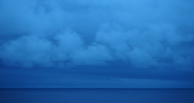 Dark blue sea meets kohl-smudge horizon in the very last light of day, a buoy light and low clouds.