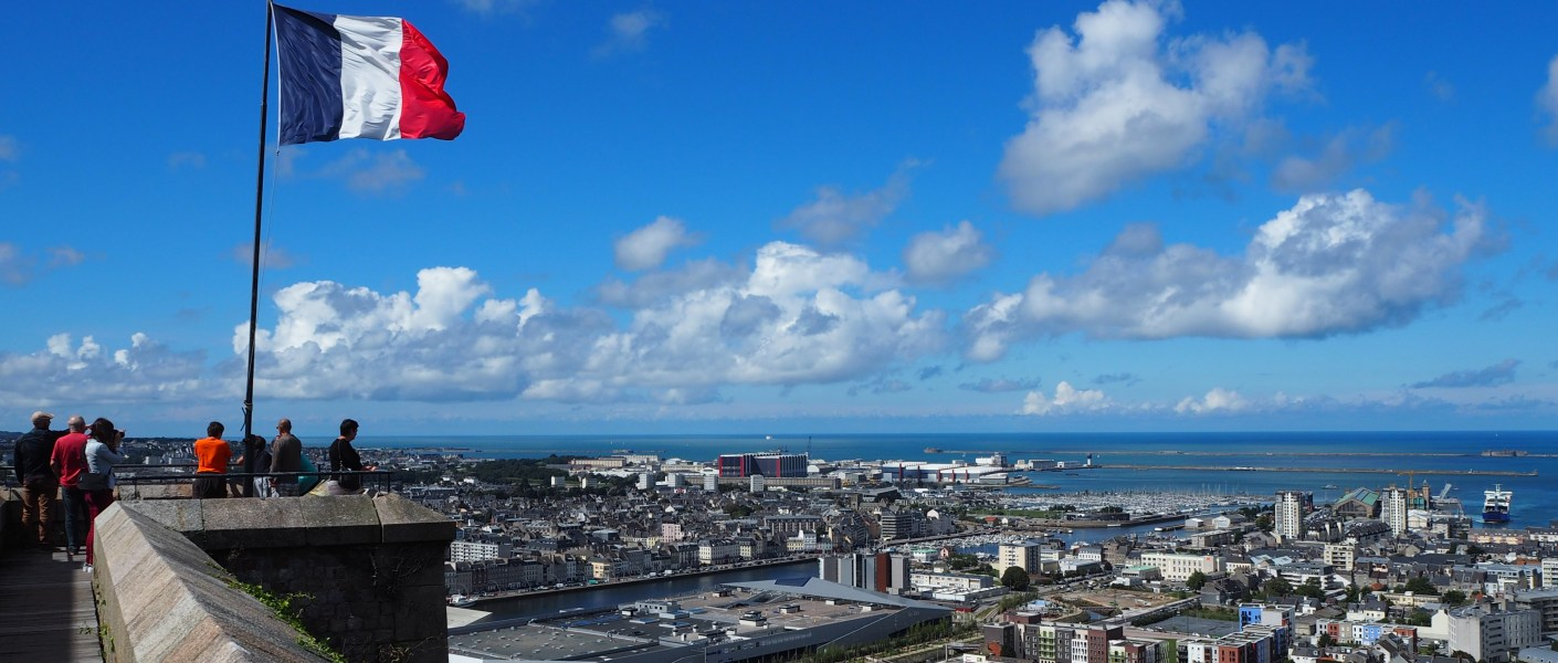 Flag of France against a blue sky above the city of Cherbourg.