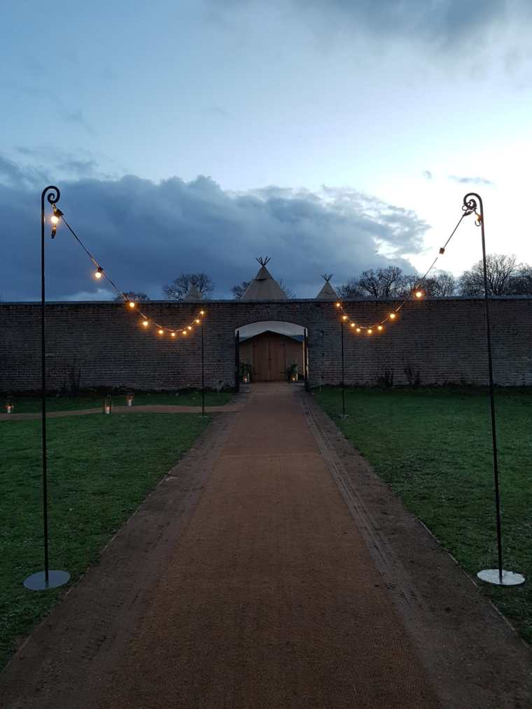 Marquee Wedding Planning - Lit walkway leading to a gateway and marquee entrance