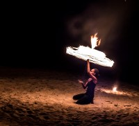 "The woman in this photo is twirling an 'umbrella' of fire. The music that accompanied this piece was Adele's ""Set Fire to the Rain""."