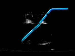 Black and white glass of water with blue straw