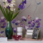 Close up image of watercolour flower panel wallpaper with butterflies behind a vase of orchids.