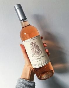 A photograph of the Great British Giffords Hall Rose, a pale pink rose with a classic English label showing a coat of arms.