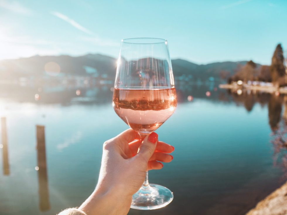 A hand holds a glass of English Rosé over a lake