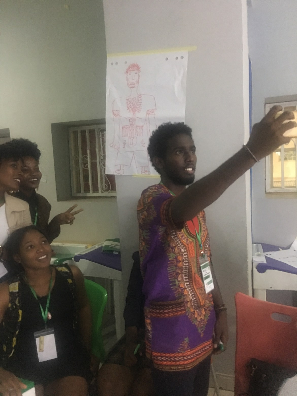 """(R-L): Motaz taking a selfie with Zuby, Ebube, Kosi & the illustrated """"Zain"""" as part of the social determinants of GBV"""